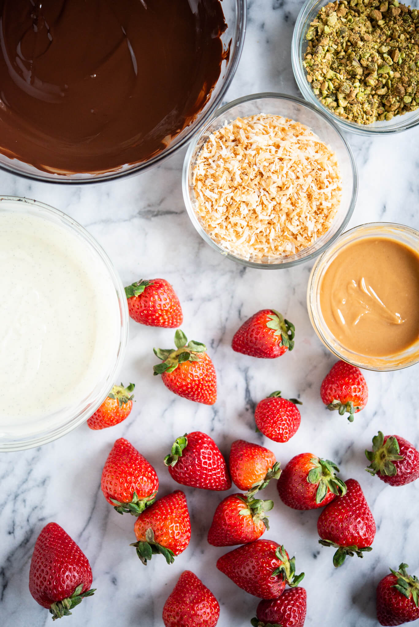 dark chocolate, white chocolate, pistachios, toasted coconut, and peanut butter in glass bowls next to strawberries on a marble surface