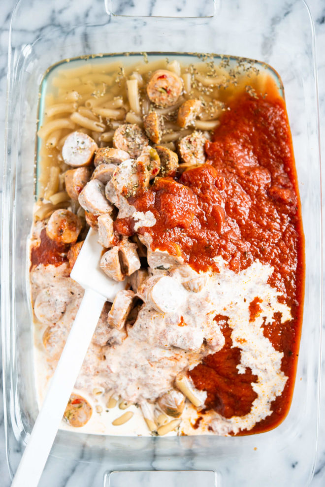 ingredients for easy pasta bake being mixed together in a glass baking dish on a marble surface