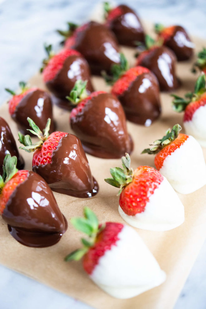 strawberries dipped in white and dark chocolate on parchment paper on a marble surface