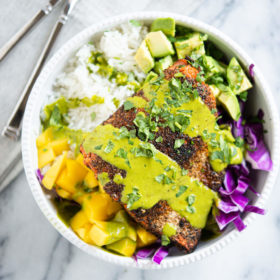 blackened salmon in a white bowl with rice, purple cabbage, mango, avocado and a green sauce sitting on a marble surface