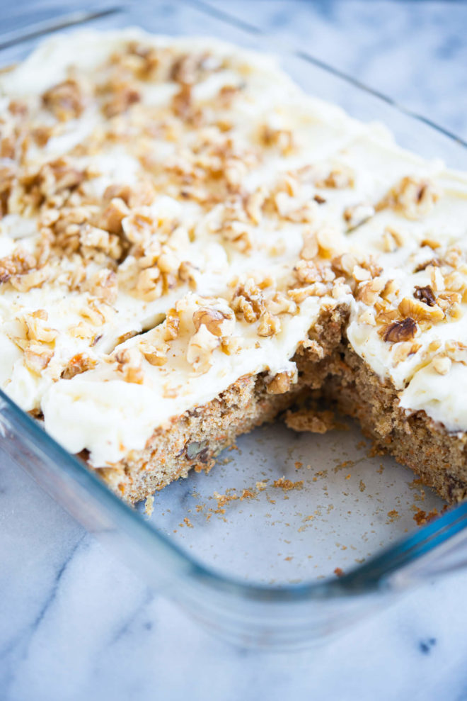 iced carrot cake cut into pieces with two pieces missing in a clear baking dish on a marble surface
