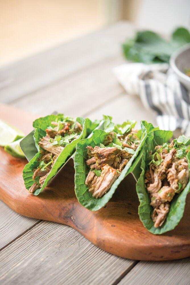 chipotle carnitas in a collard green wrap on a wooden table - crock pot freezer meals