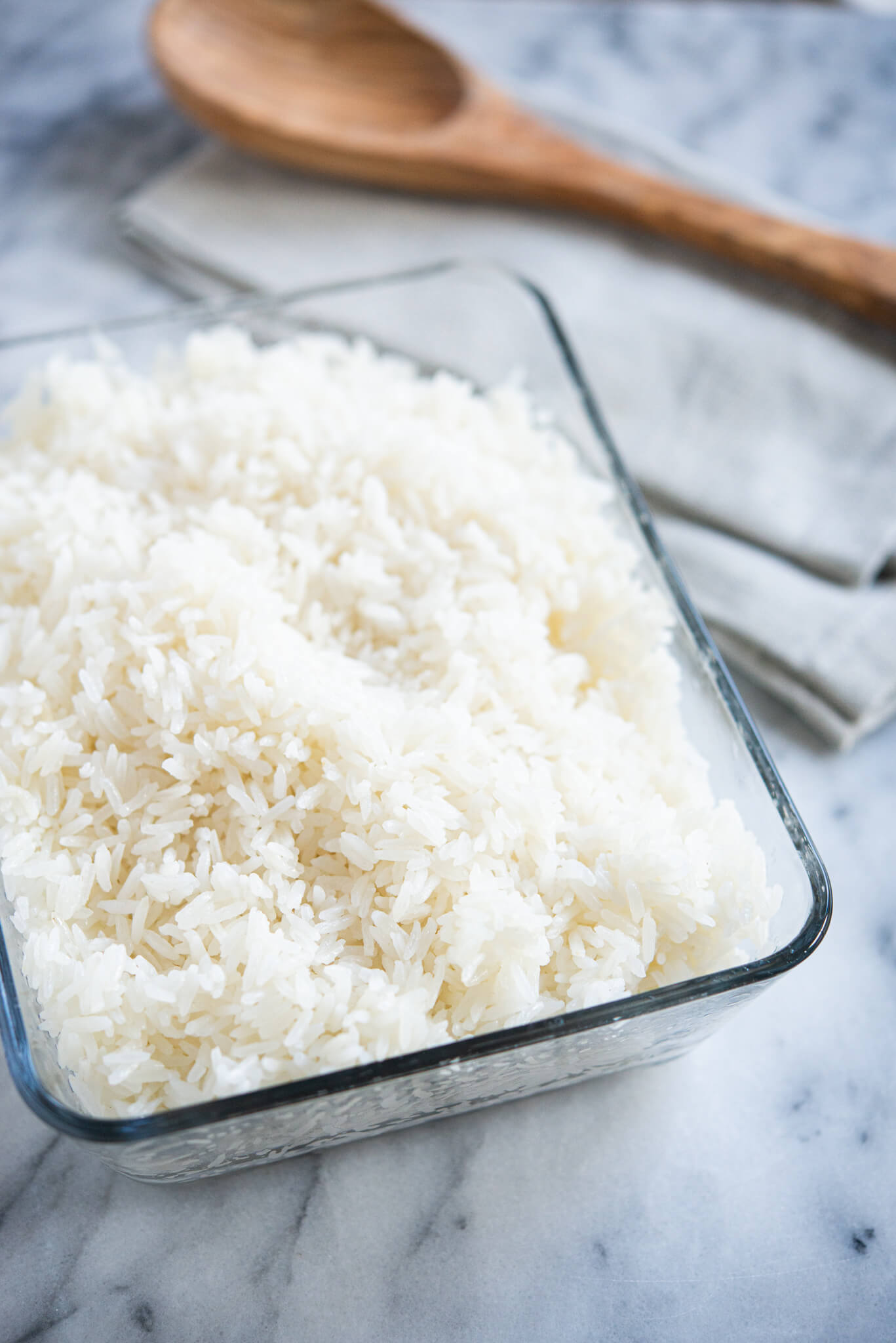 cooked white coconut rice in a glass dish with a wooden spoon on a marble surface