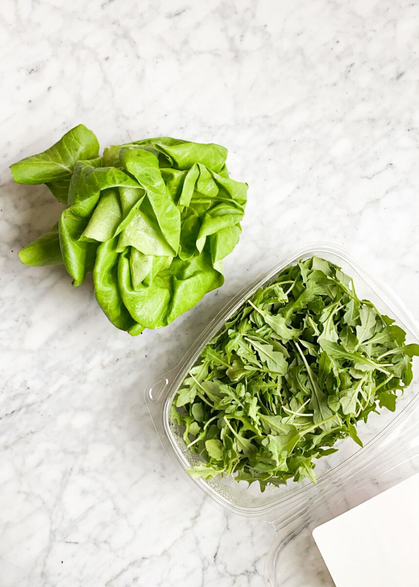 a clear open tub of arugula sitting next to a head of bibb lettuce on a marble surface