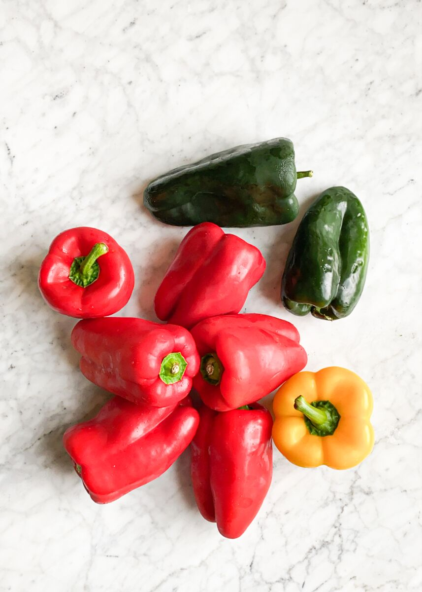 red, yellow, and green peppers laying on a marble surface