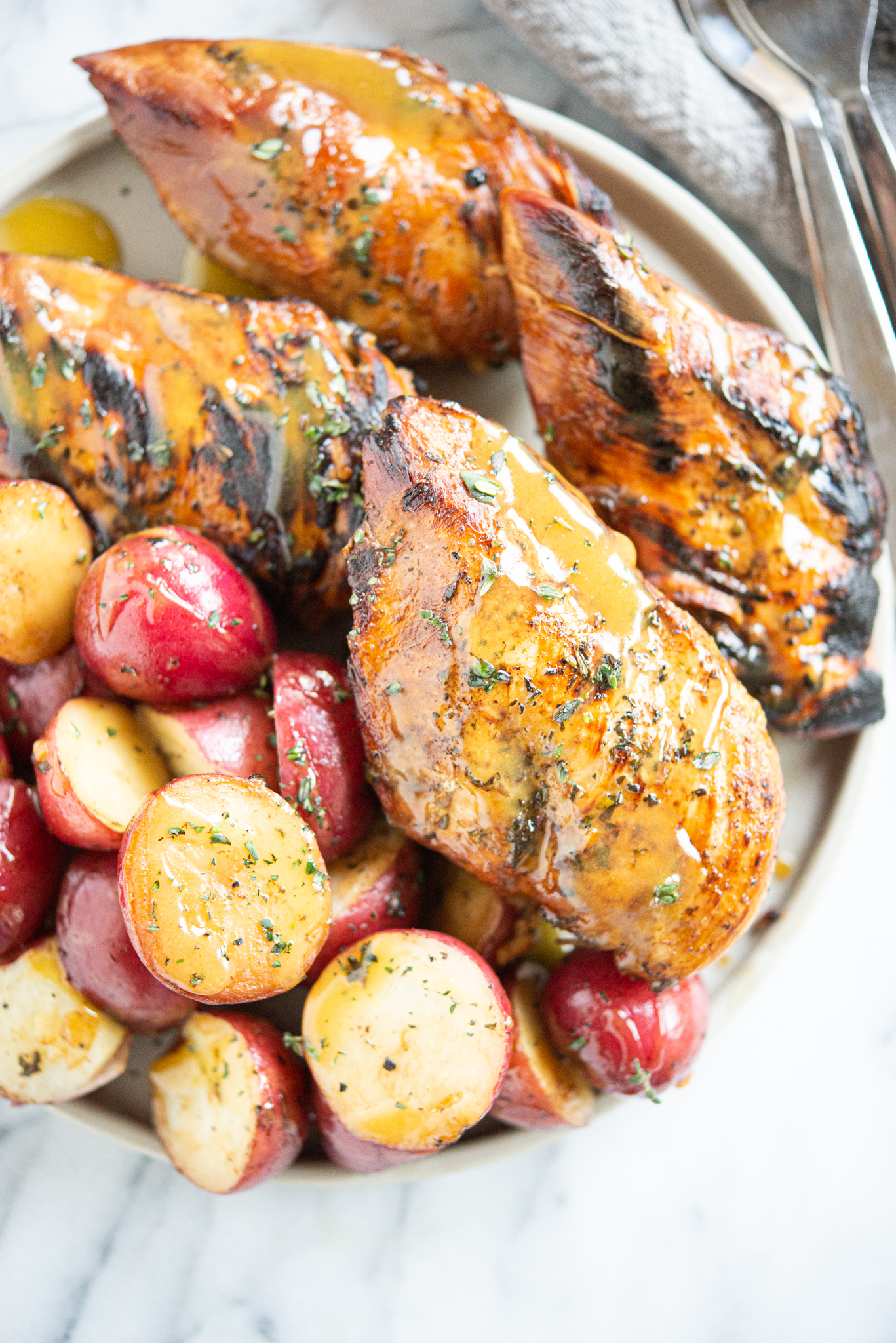Seared honey mustard chicken and halved red potatoes on a grey plate on a marble surface