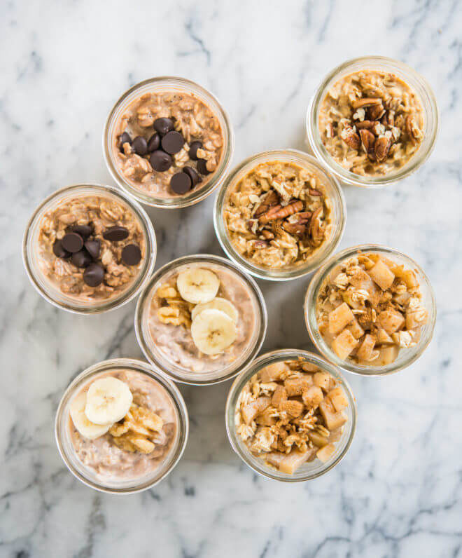 8 glass mason jars filled with overnight oats with various toppings like diced apples, sliced bananas, chocolate chips, and pecans on a marble surface
