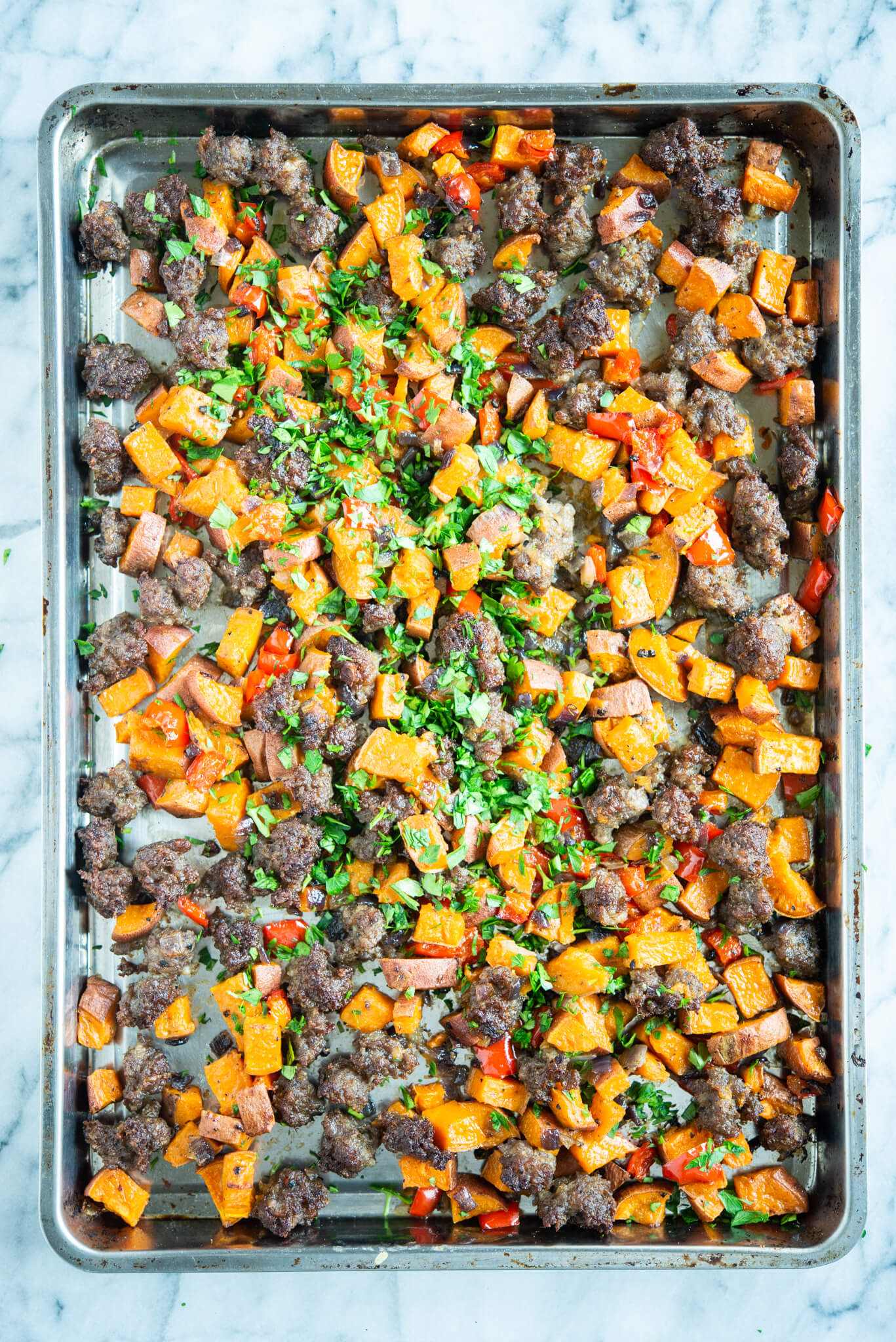 sweet potato hash - crumbled sausage, bell pepper, and sweet potato breakfast hash on a sheet pan on a marble surface