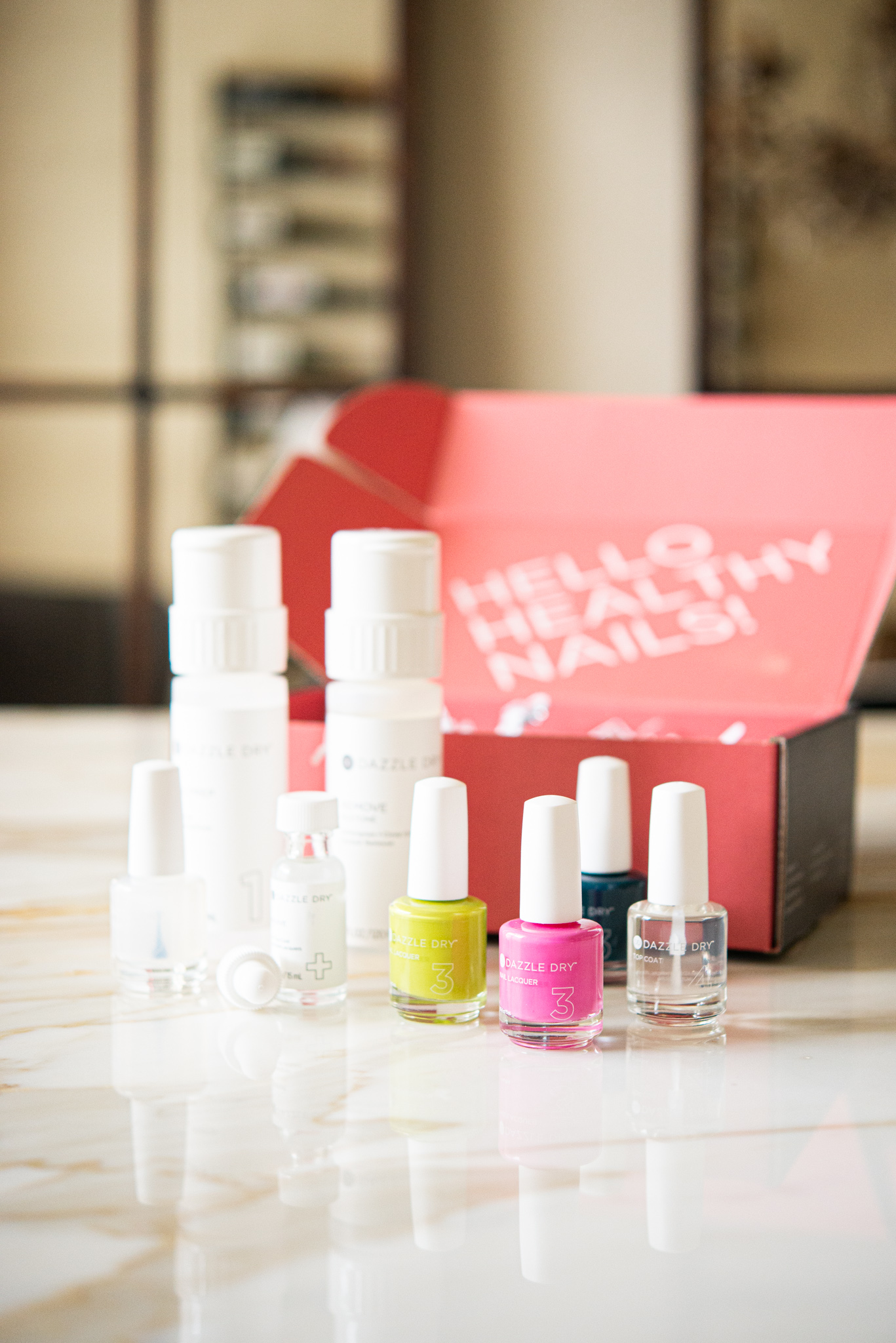 dazzle dry nail kit with three nail polishes, a top coat, and a remover, in front of a bright pink box