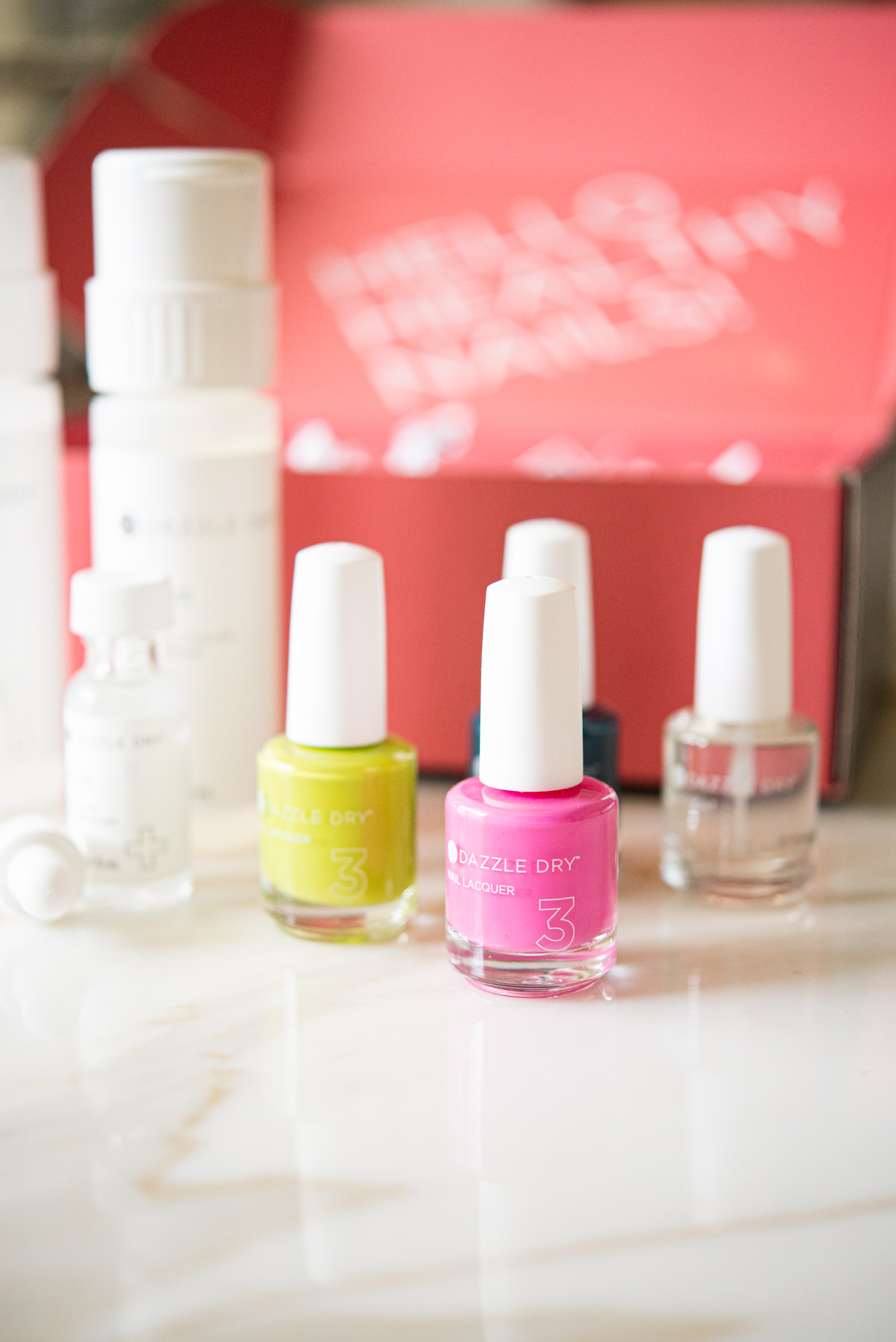 pink nail polish with yellow and clear polish behind it in front of a pink box - dazzle dry nail system