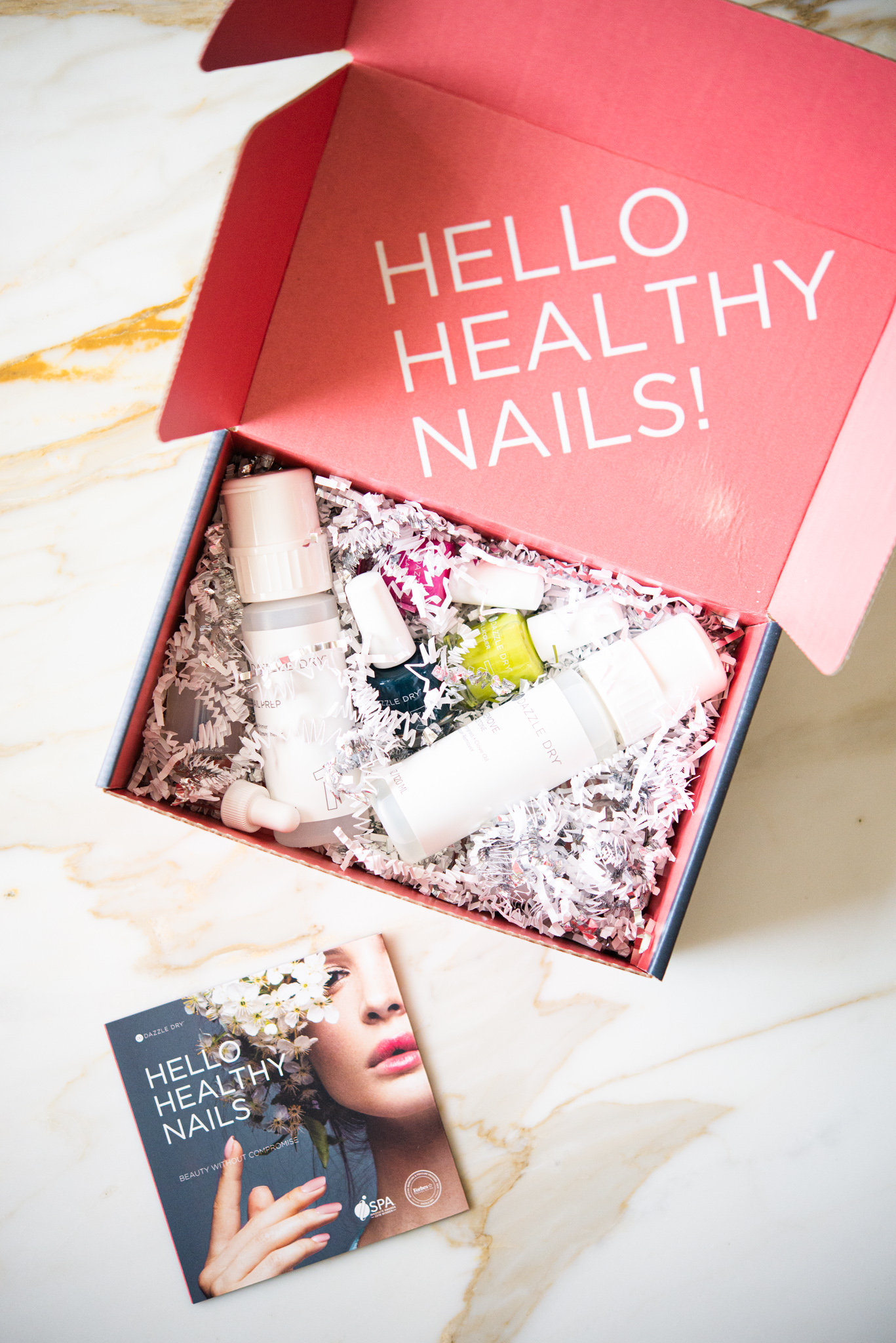pink box filled with 3 colors of nail polish, two clear polishes, and polish remover on a marble surface