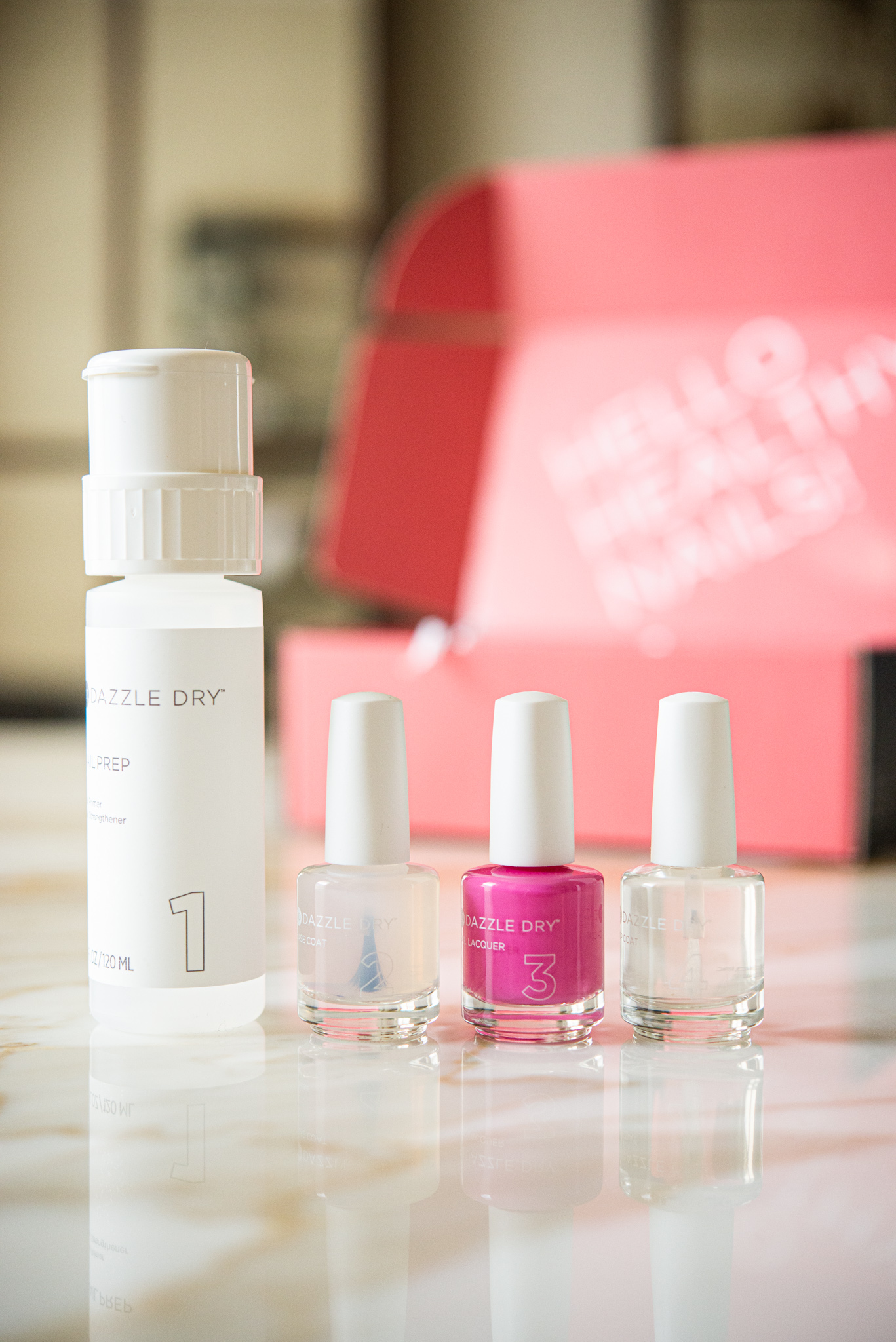 dazzle dry nail system - bright pink nail polish next to two clear nail polishes and a remover, on a marble table