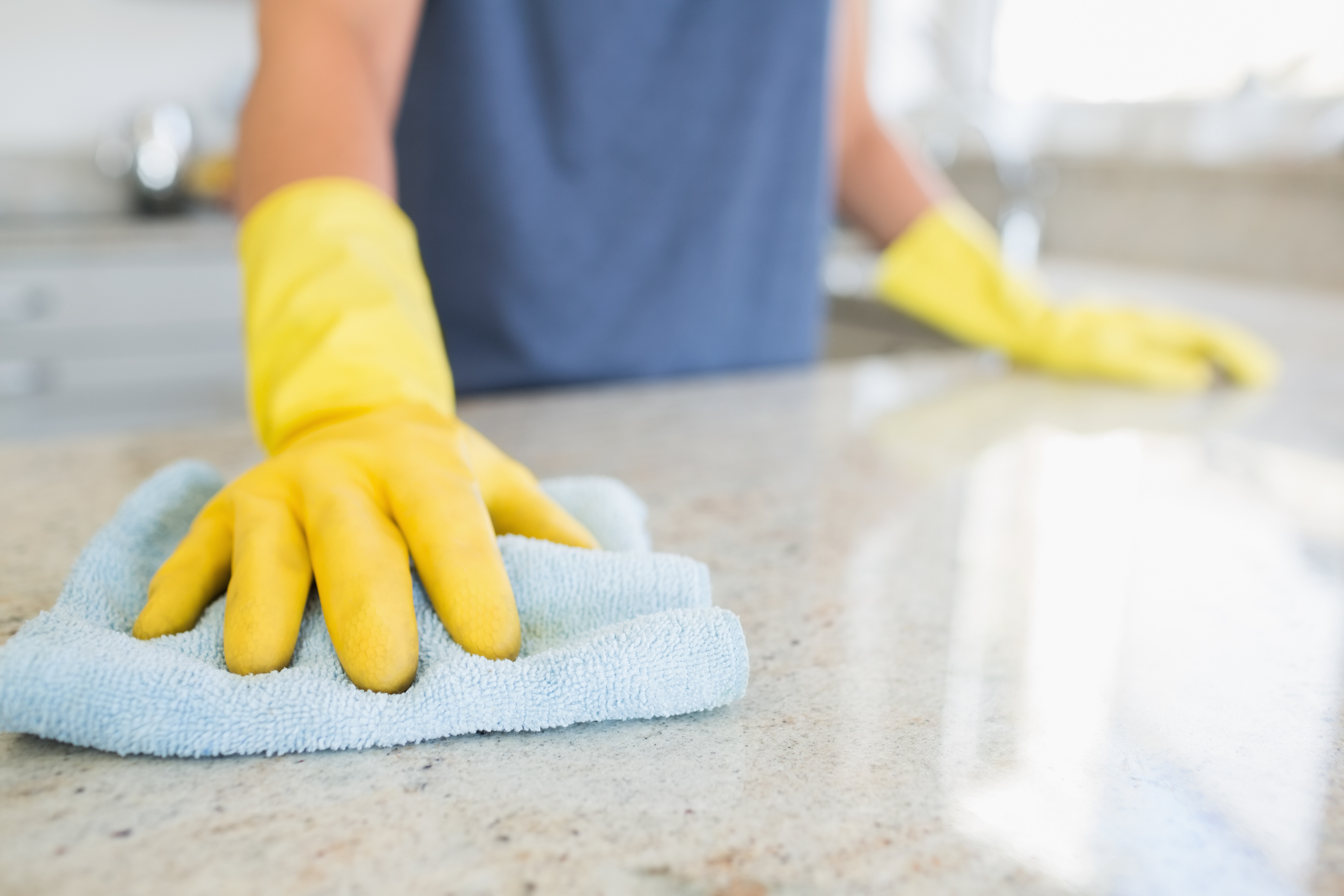 woman wearing yellow cleaning gloves wiping kitchen counter with blue towel