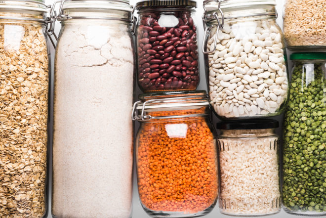 Variety of grains and legumes in glass jars, top view