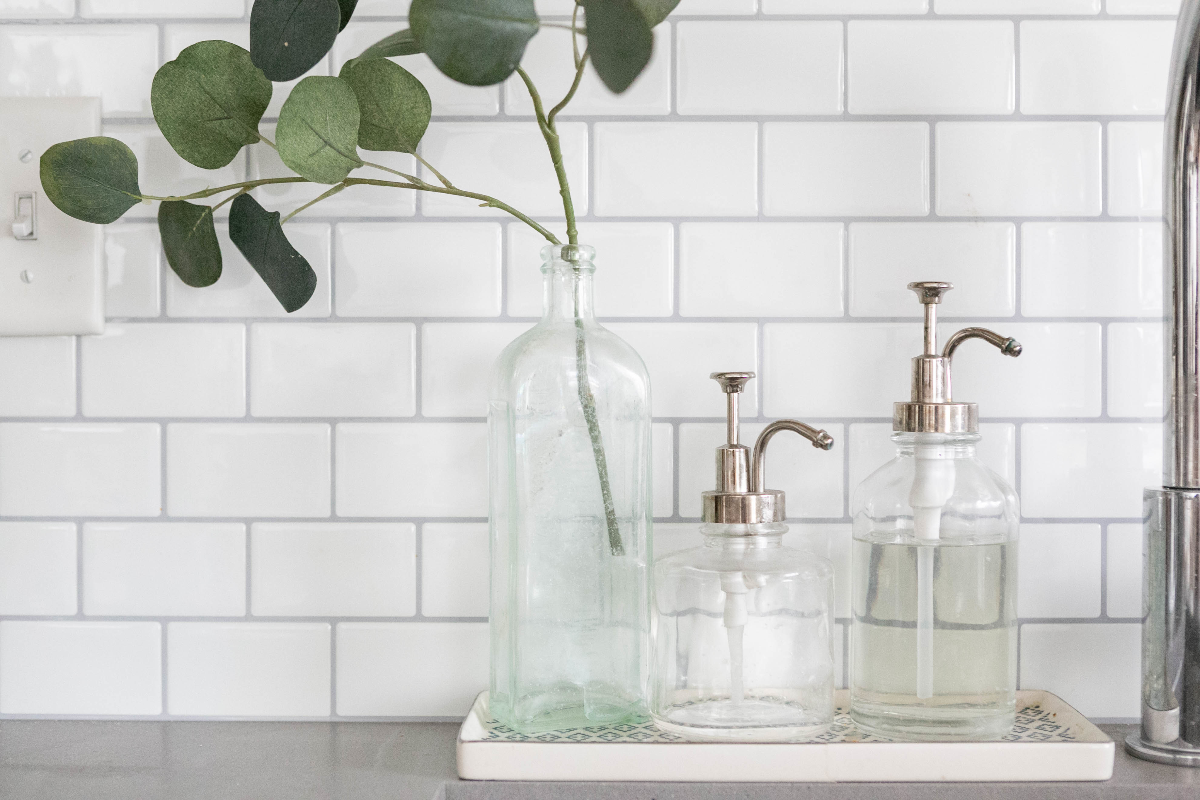 glass bottles with clear soap in a kitchen next to a clear jar with a green plant in it