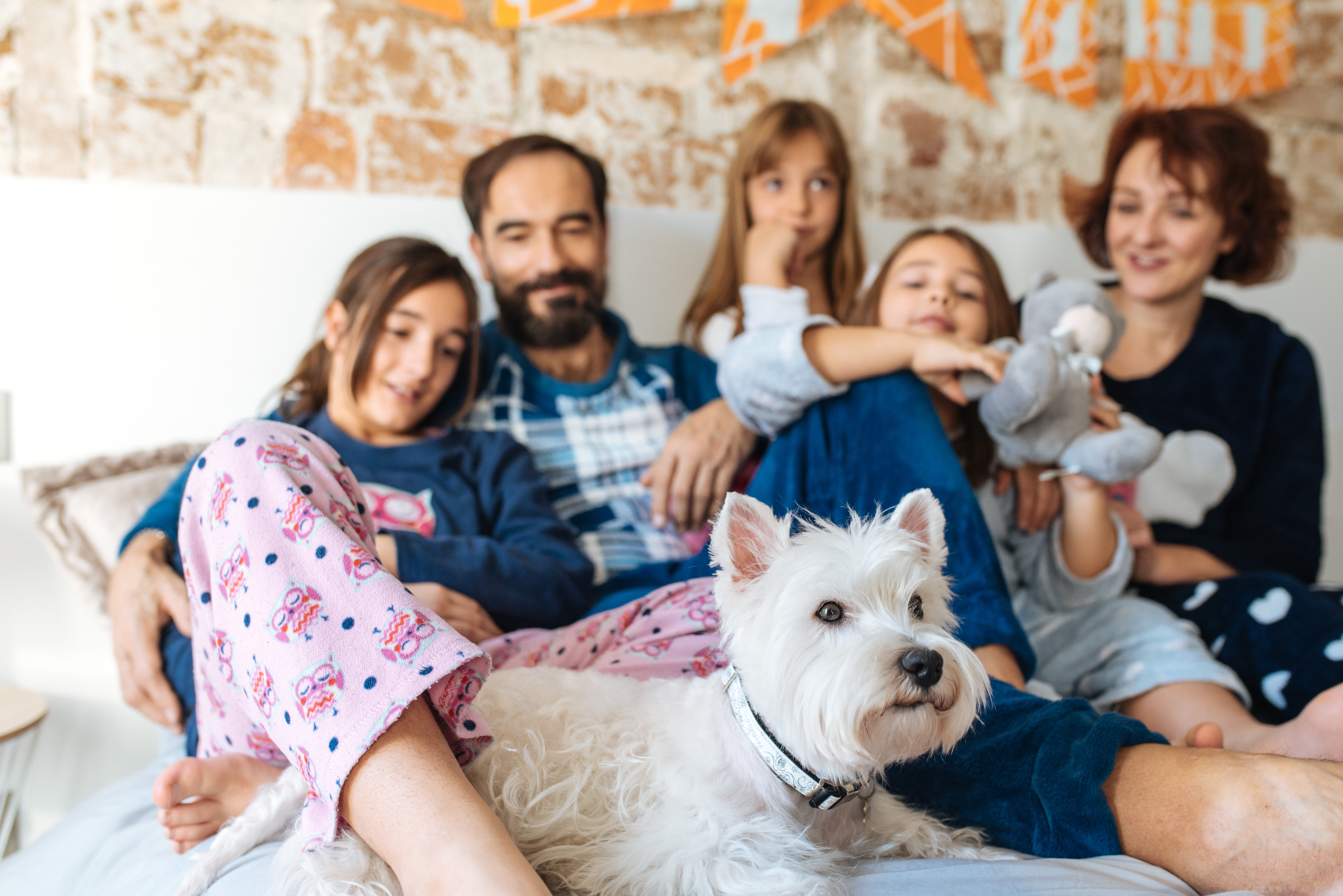 Mature couple relaxed at home in bed with their four little daughters and the Dog