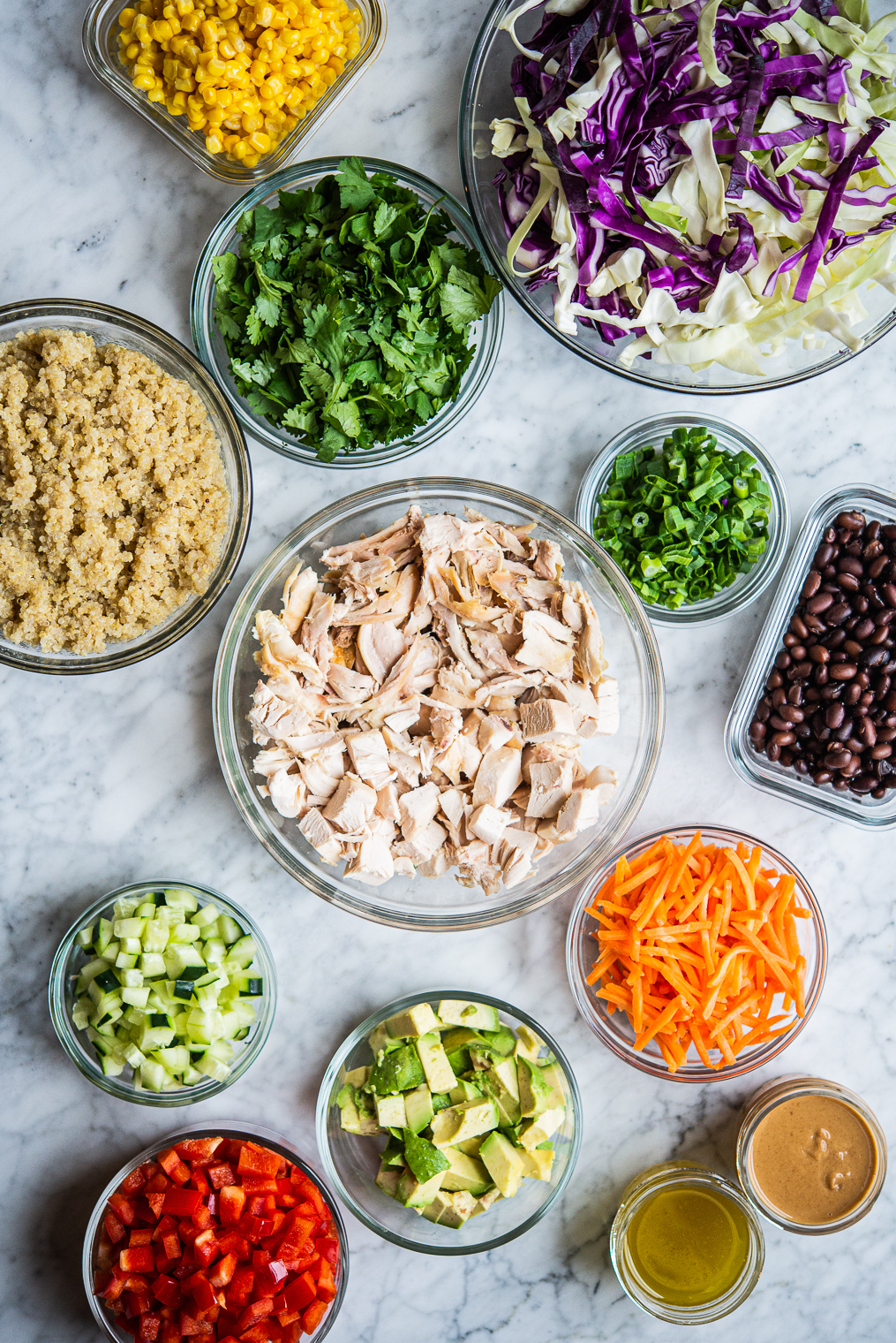 meal prep ingredients for thai chicken salad and southwestern quinoa salad in separate clear containers on a marble surface