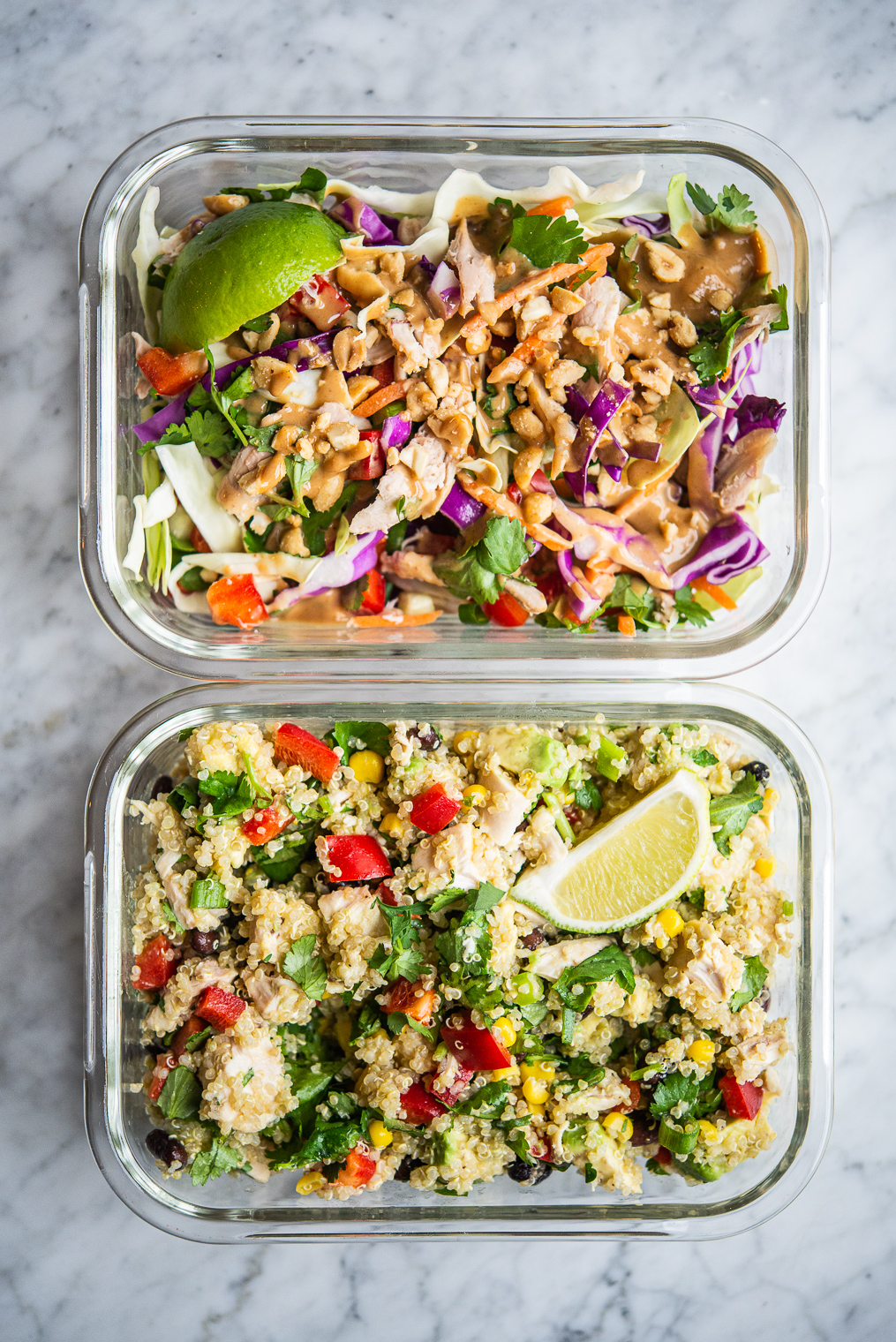 thai chicken salad and southwestern quinoa salad in clear individual portion containers on a marble surface