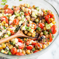mediterranean chickpea salad - chickpeas, feta cheese, tomatoes, and cucumber - in a glass bowl on a marble surface with a wooden spoon inside
