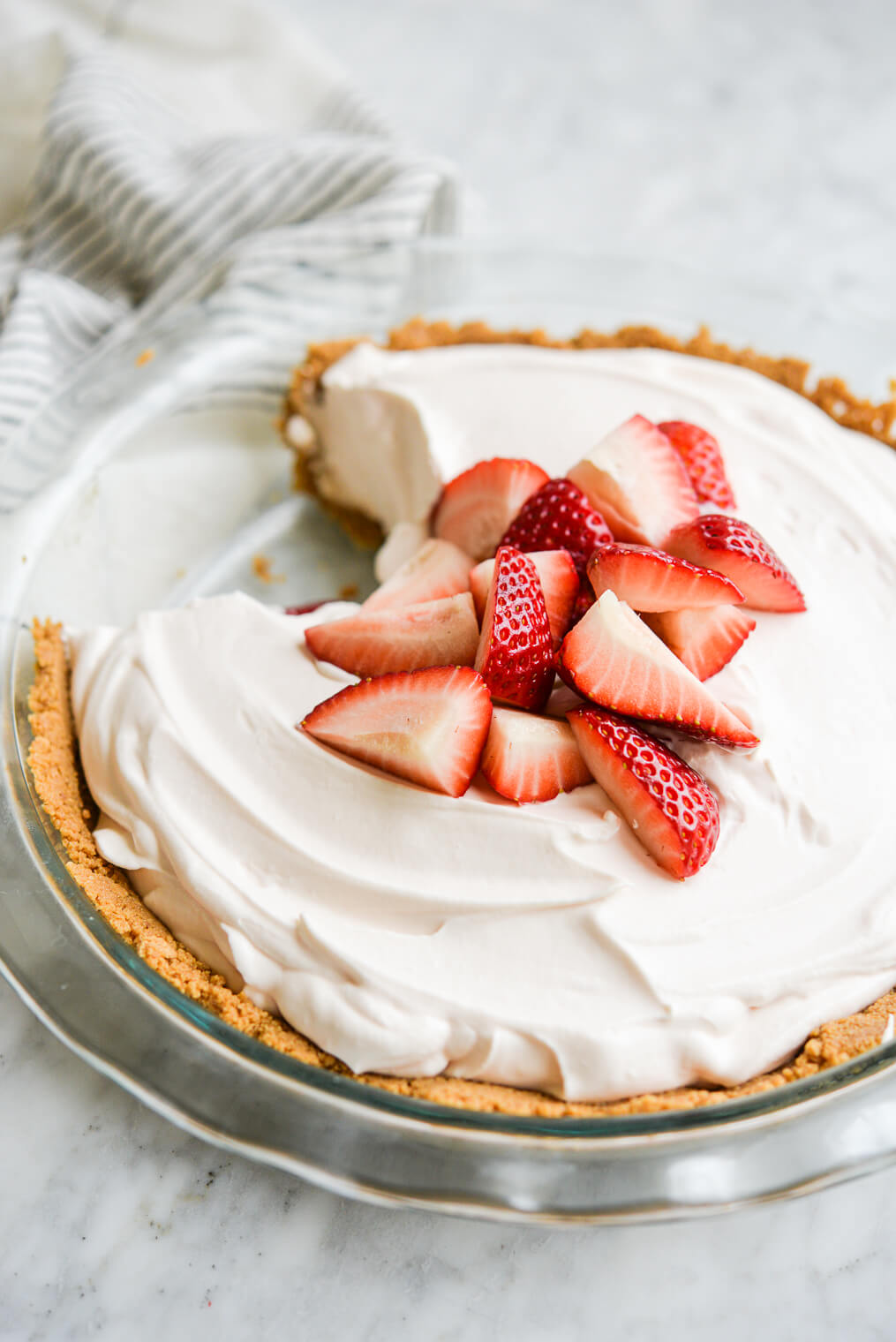 strawberry yogurt pie in a graham cracker crust with chopped strawberries on top