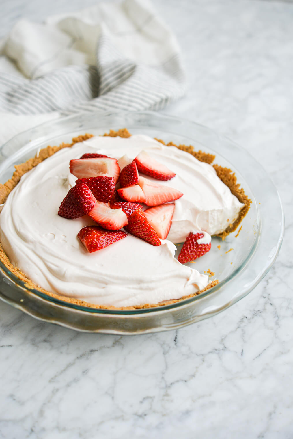 strawberry yogurt pie with a slice taken out of it topped with quartered strawberries on a marble surface