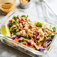 colorful thai chopped chicken salad in an individual serving glass meal prep container with peanut dressing + crushed peanuts in the background