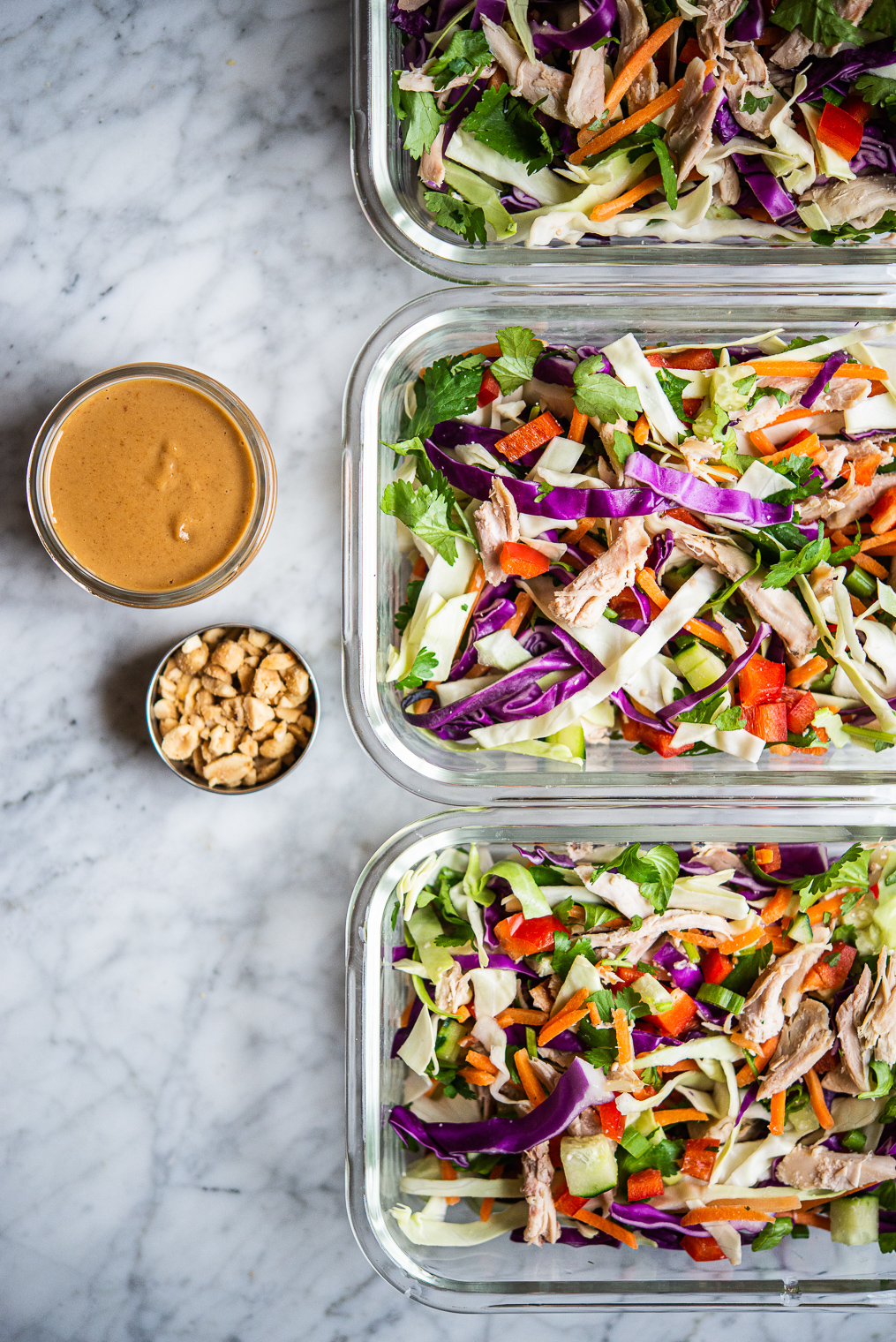 colorful thai chopped chicken salad in 3 individual serving glass meal prep containers sitting next to peanut dressing + crushed peanuts