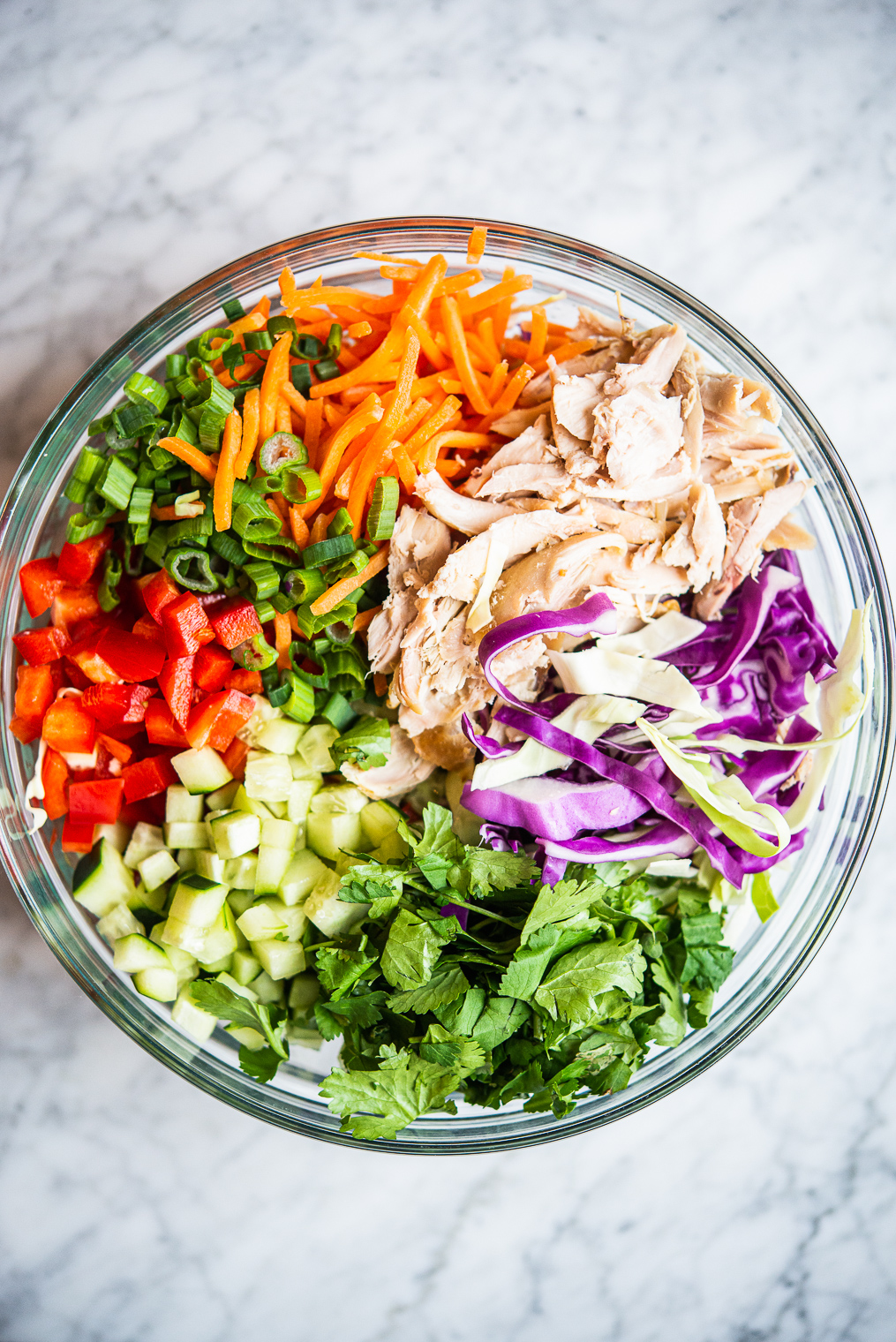 thai chopped chicken salad ingredients: carrots, cucumber, bell pepper, cabbage, chicken, and cilantro in a large glass bowl on a marble surface