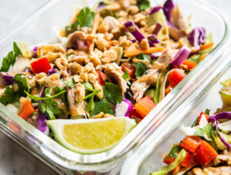 colorful thai chopped chicken salad in 2 individual serving glass meal prep containers