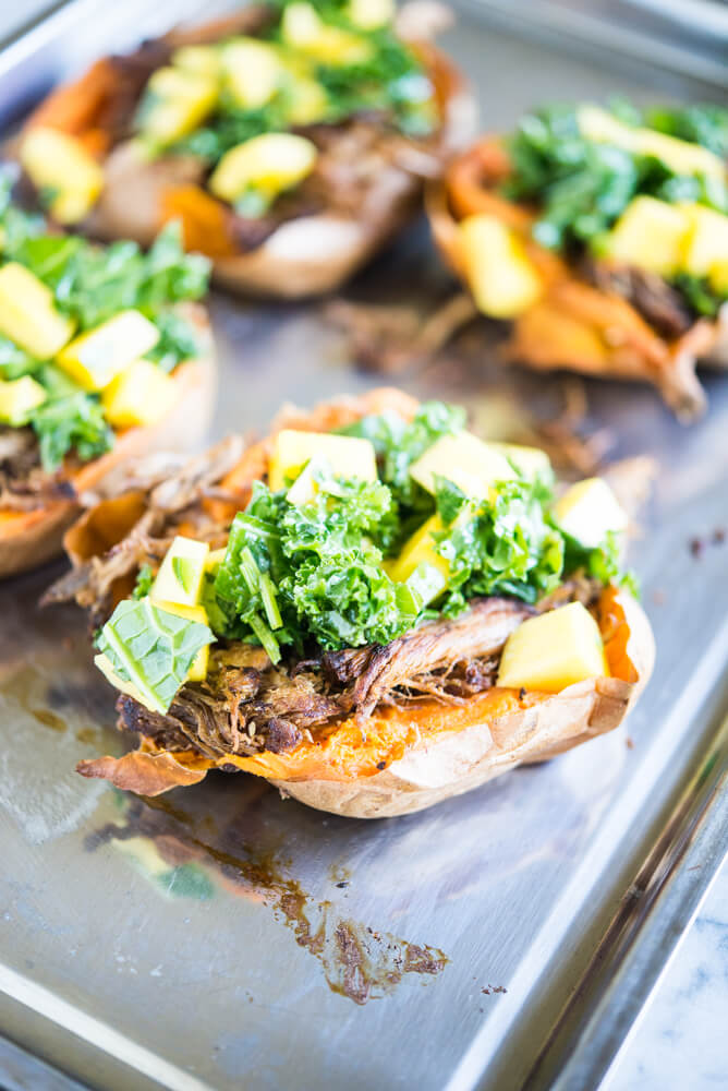 sweet potatoes stuffed with shredded jerk pork topped with kale and mangoes on a stainless steel sheet pan