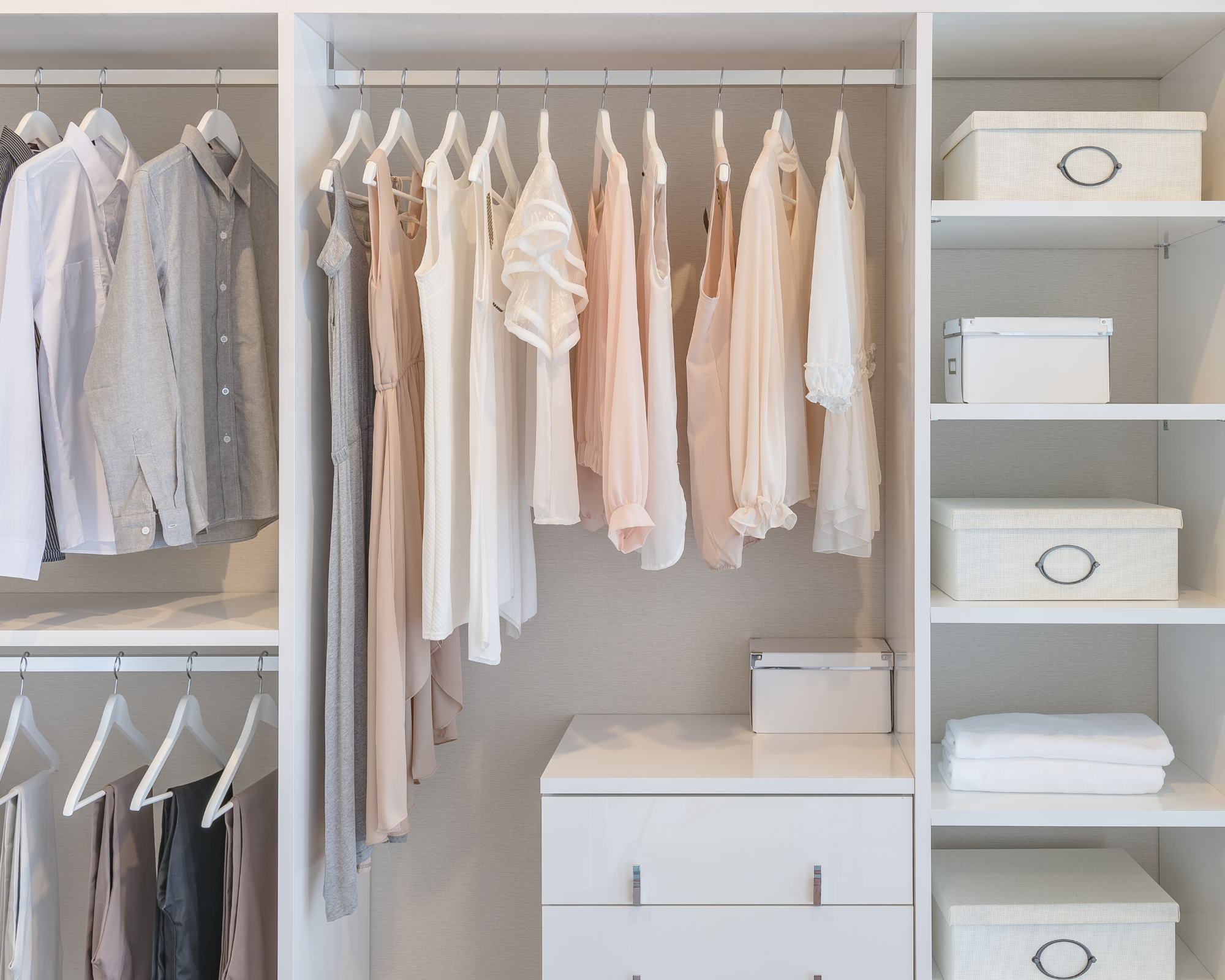 organized closet with white and pink shirts, a dresser, and white boxes