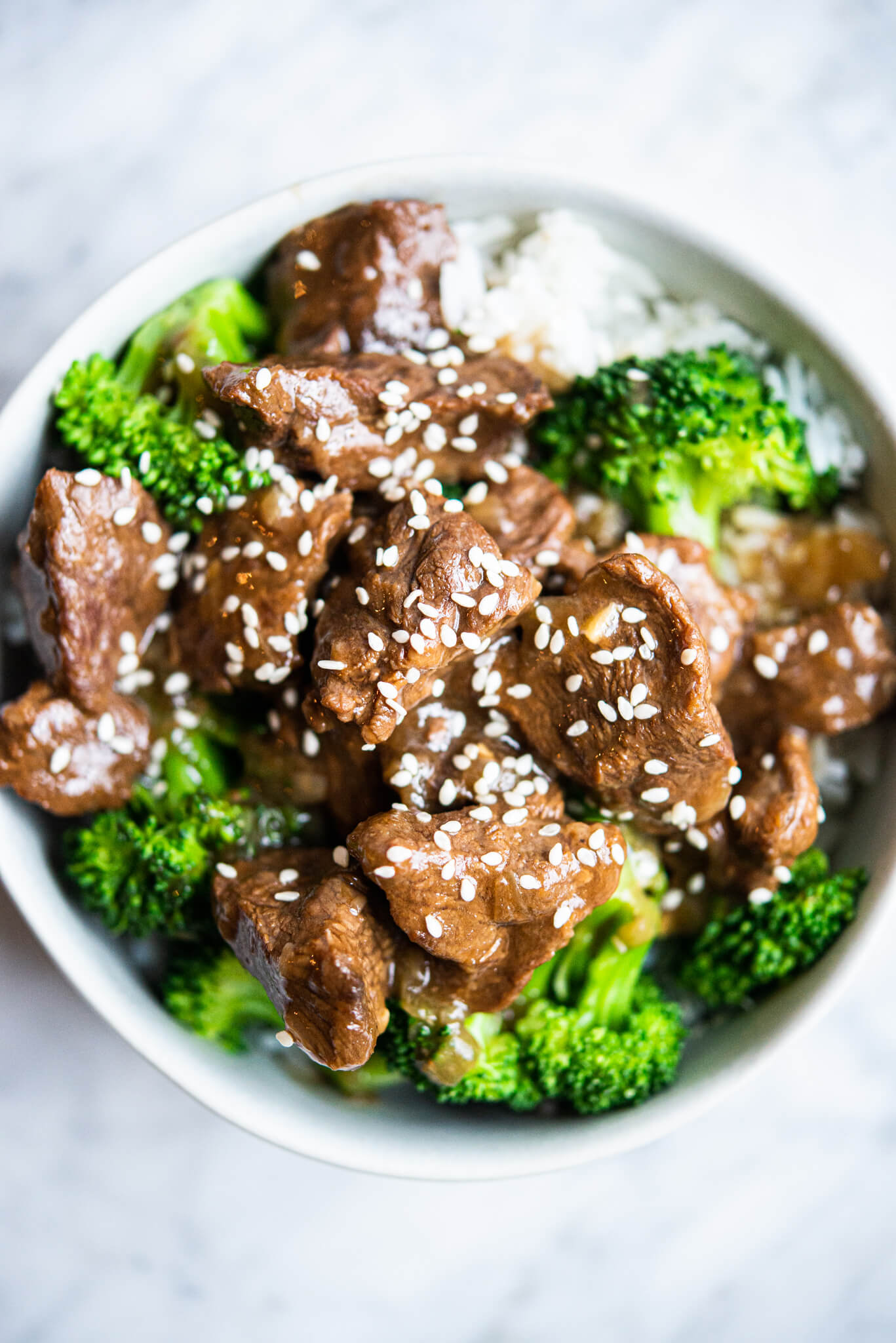 instant pot beef and broccoli over white rice in a white bowl on a marble surface