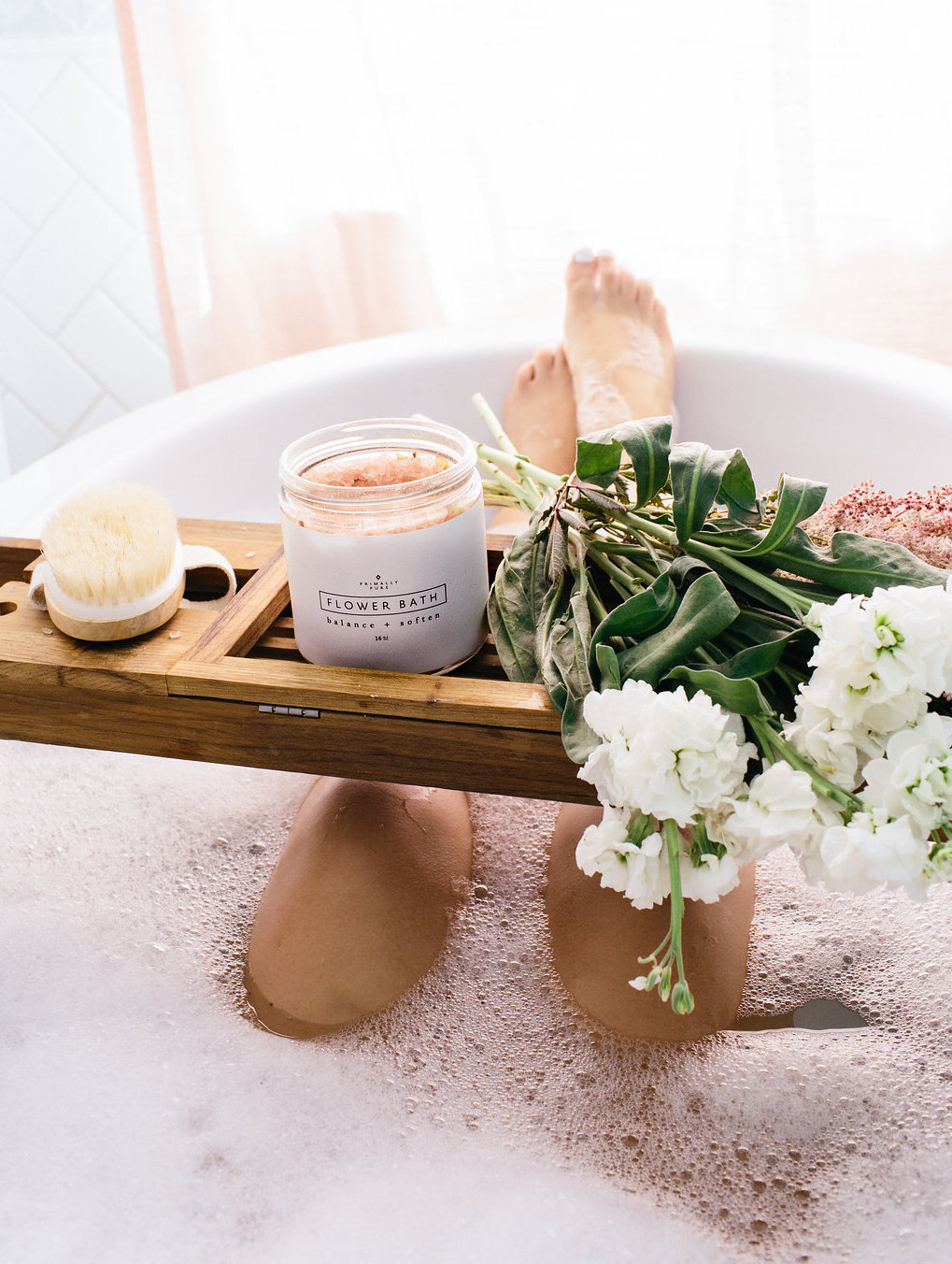 spa day at home - bubble bath with a wooden tub stand with flowers and bath soak