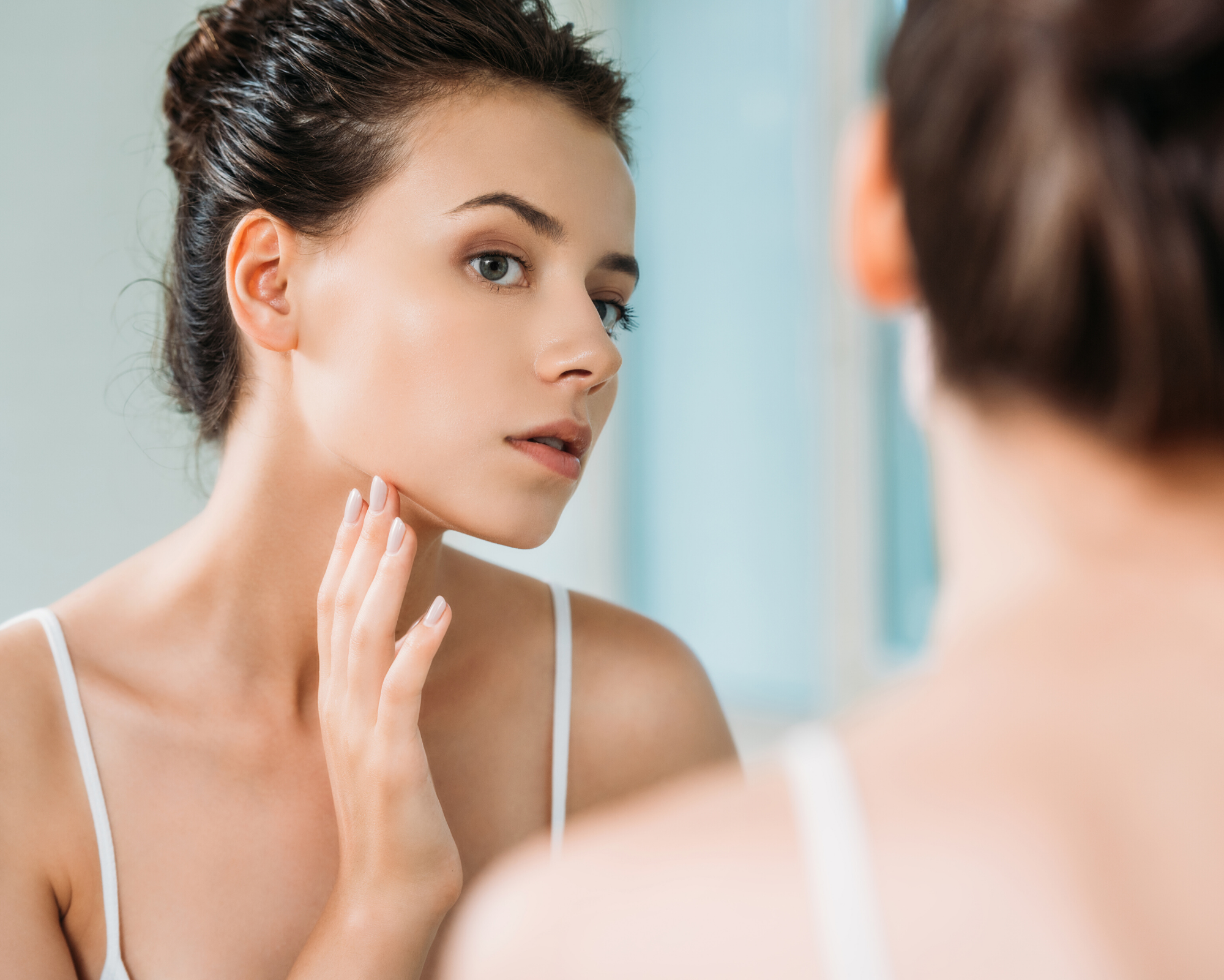 woman looking in mirror touching face