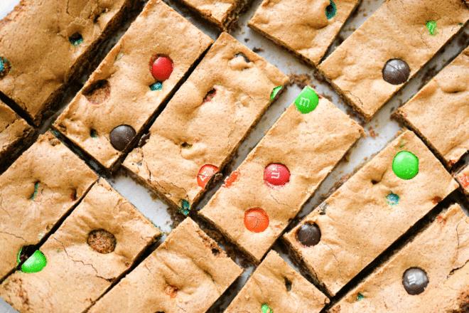 M&M cookie bars cut into rectangles on parchment paper