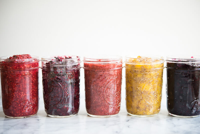 side view of 5 mason jars with different colored chia jam
