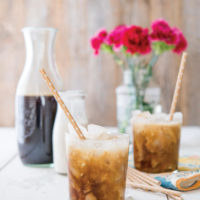 two cups of cold brew coffee with with paper straws in front of a wooden background with a pitcher of cold brew, cream, and pink flowers