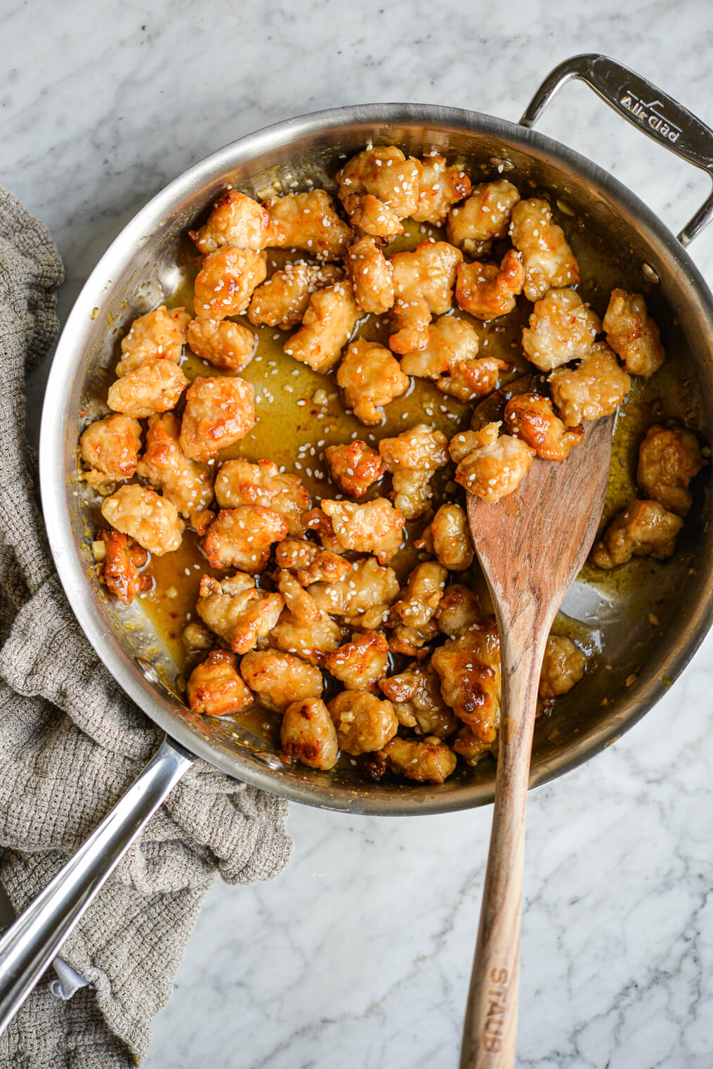 general tso's chicken in a stainless pan with a wooden spoon on a marble surface