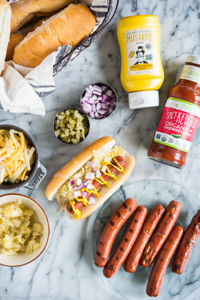 hot dogs, buns, mustard, ketchup, cheese, relish, and onions ready for a hot dog bar on a marble surface