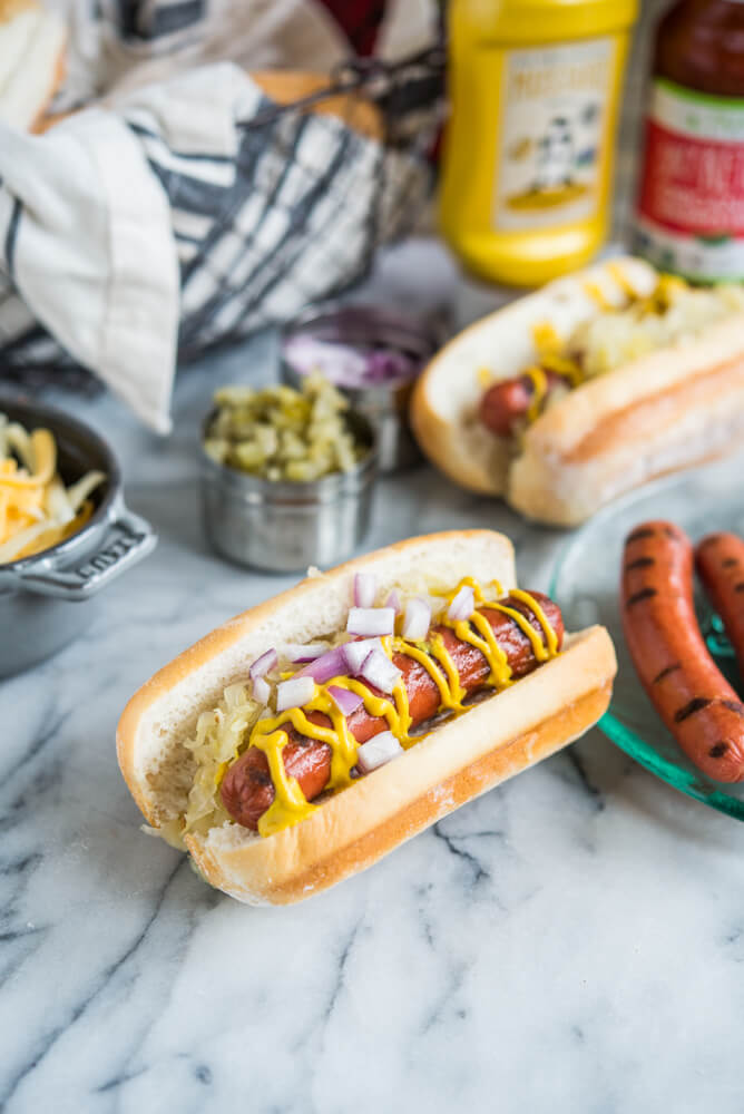 two hot dogs with sauerkraut, red onions, and mustard next to other toppings on a marble surface