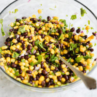 corn and black bean salsa in a large glass bowl with a metal spoon on a marble surface