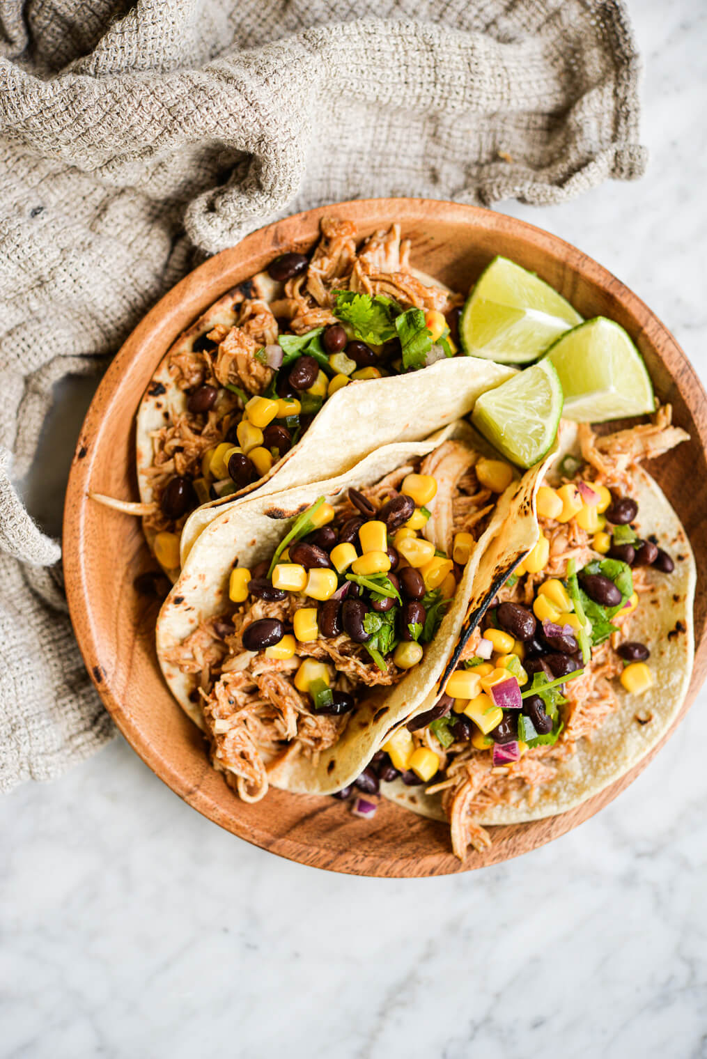 three instant pot bbq chicken tacos topped with black bean and corn salsa on a wooden plate on a marble surface