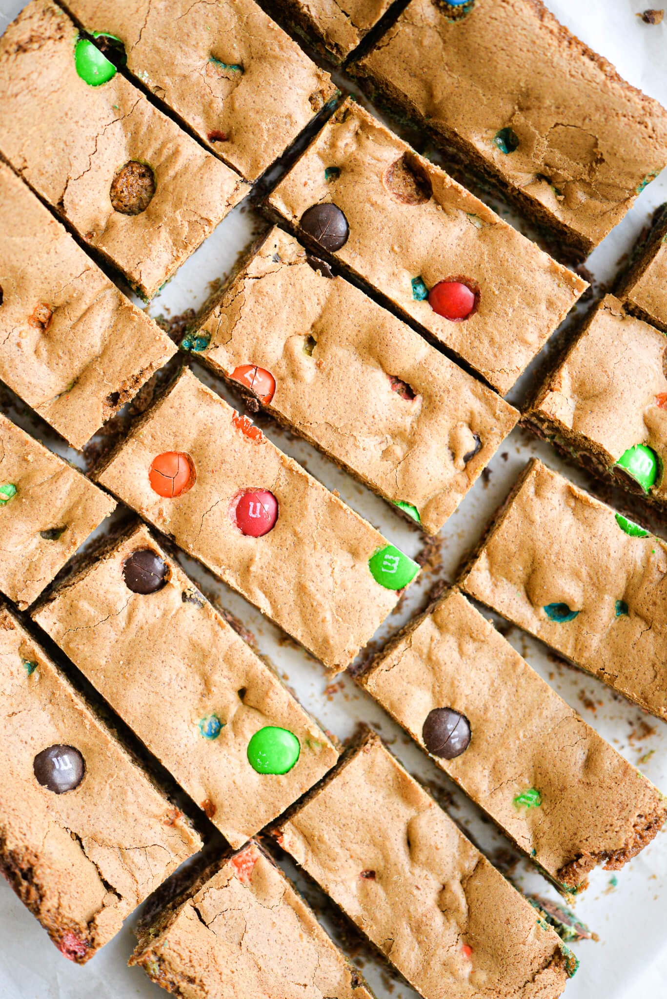 already cut m&m cookie bars spread out on parchment paper