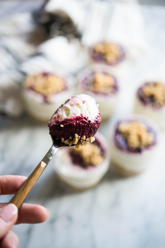 a spoonful of no-bake cheesecake with jars of no bake cheesecake sitting on a marble surface in the background