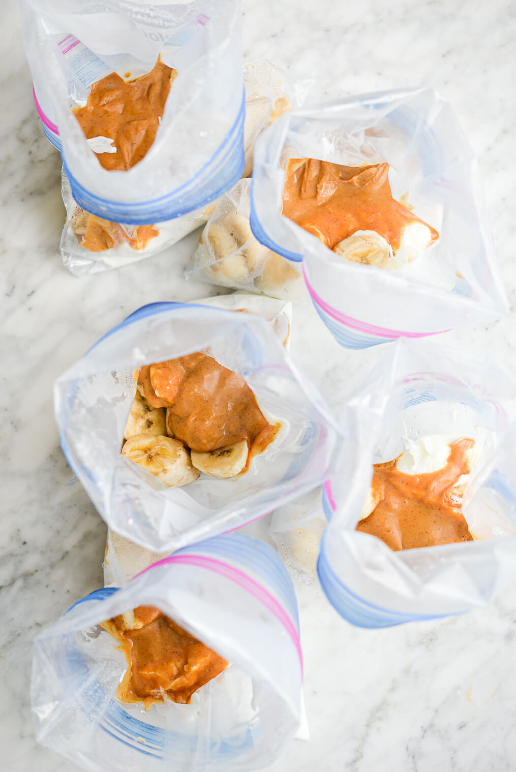 5 open peanut butter banana smoothie packs laying on a marble surface
