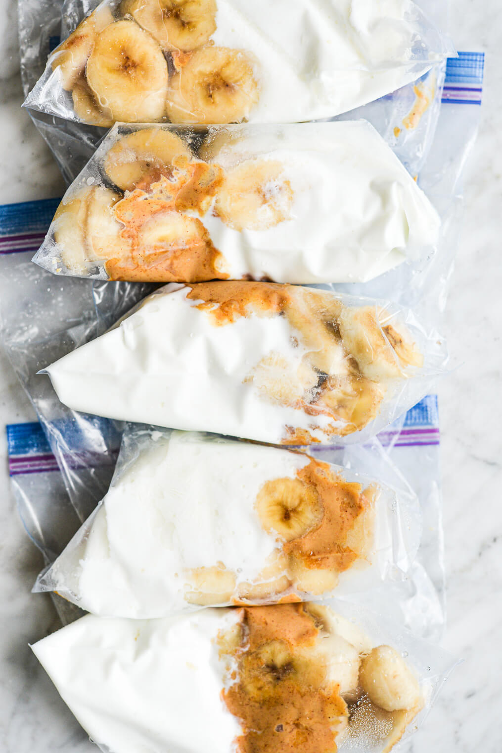 5 peanut butter banana smoothie packs laying on a marble surface ready to go in the freezer
