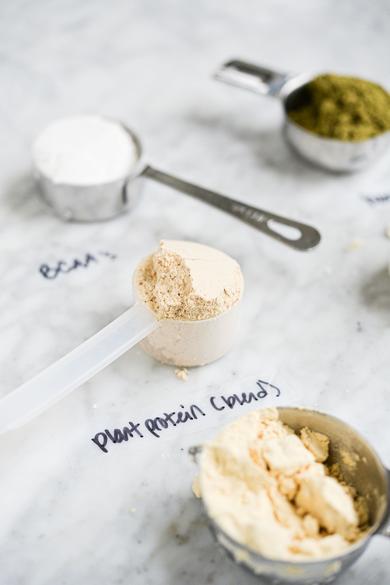 different protein powders in scoops or measuring cups with labels on a marble surface