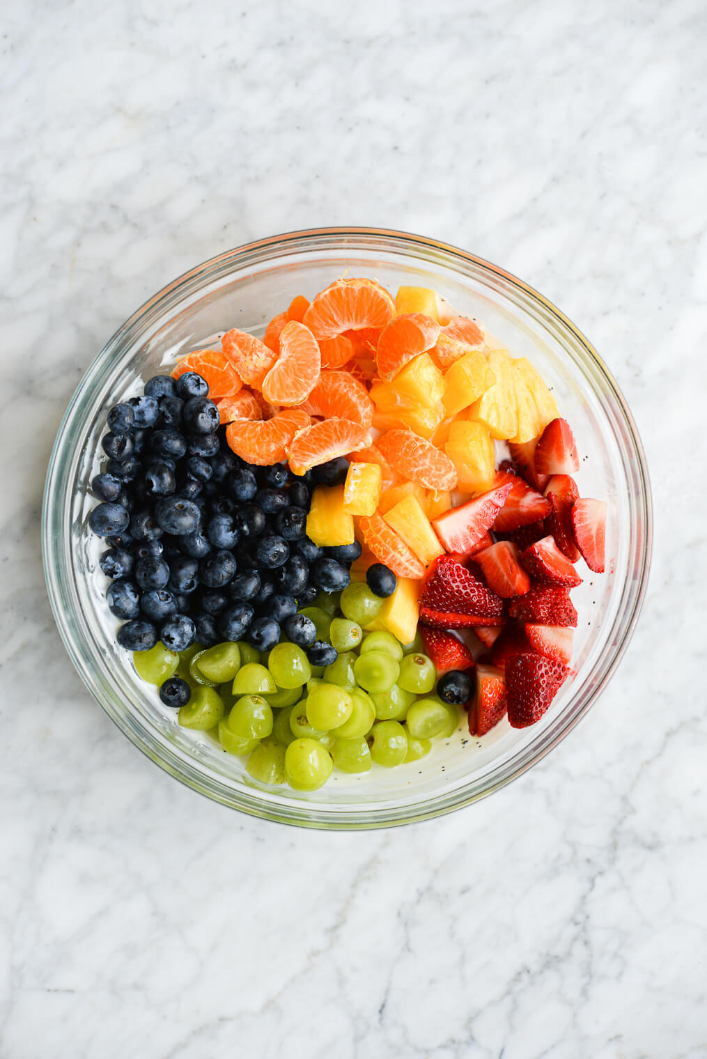 the fruit for a fruit salad (oranges, strawberries, grapes, and blueberries) in a clear bowl on a marble surface