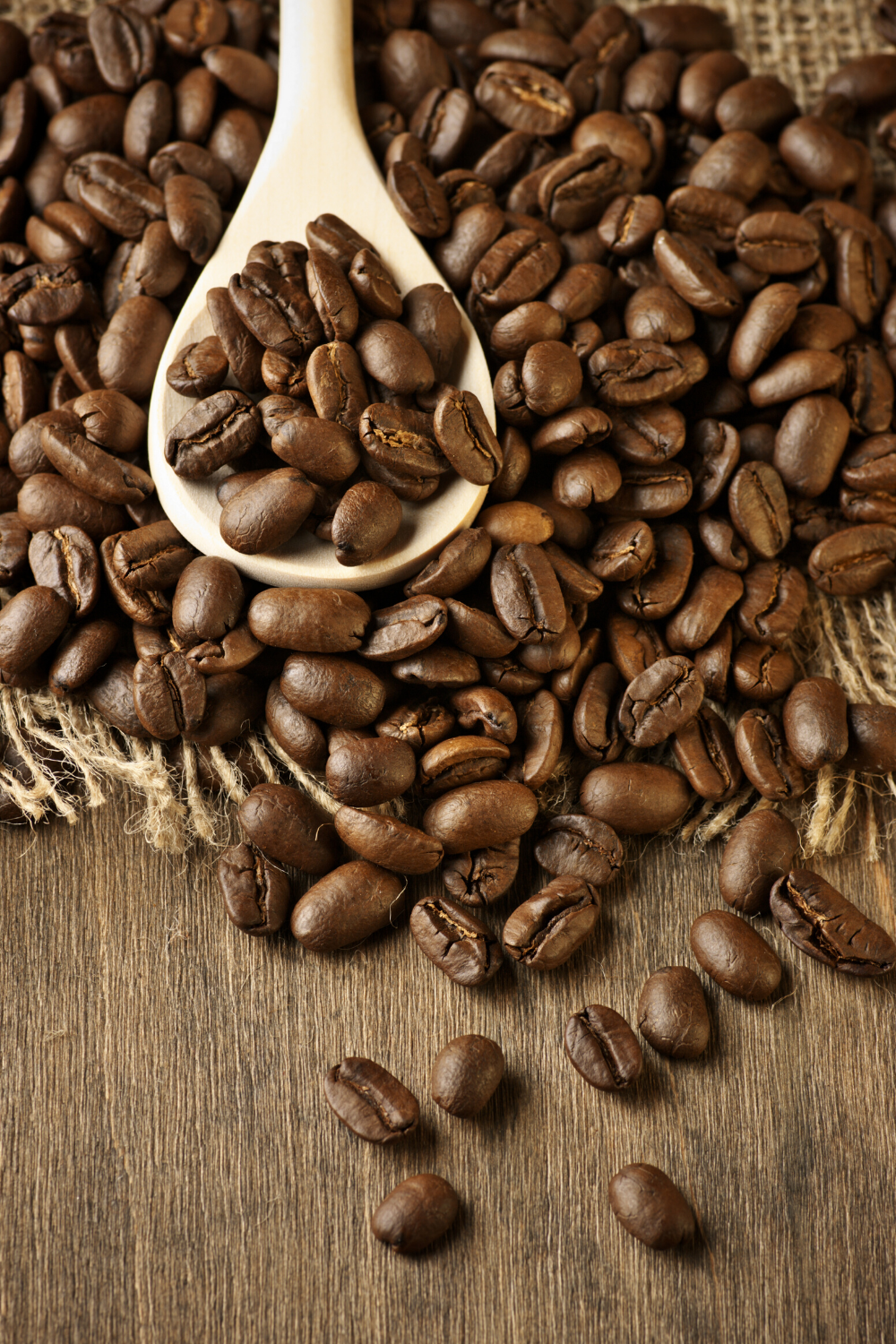 coffee beans on a wooden surface with a wooden spoon