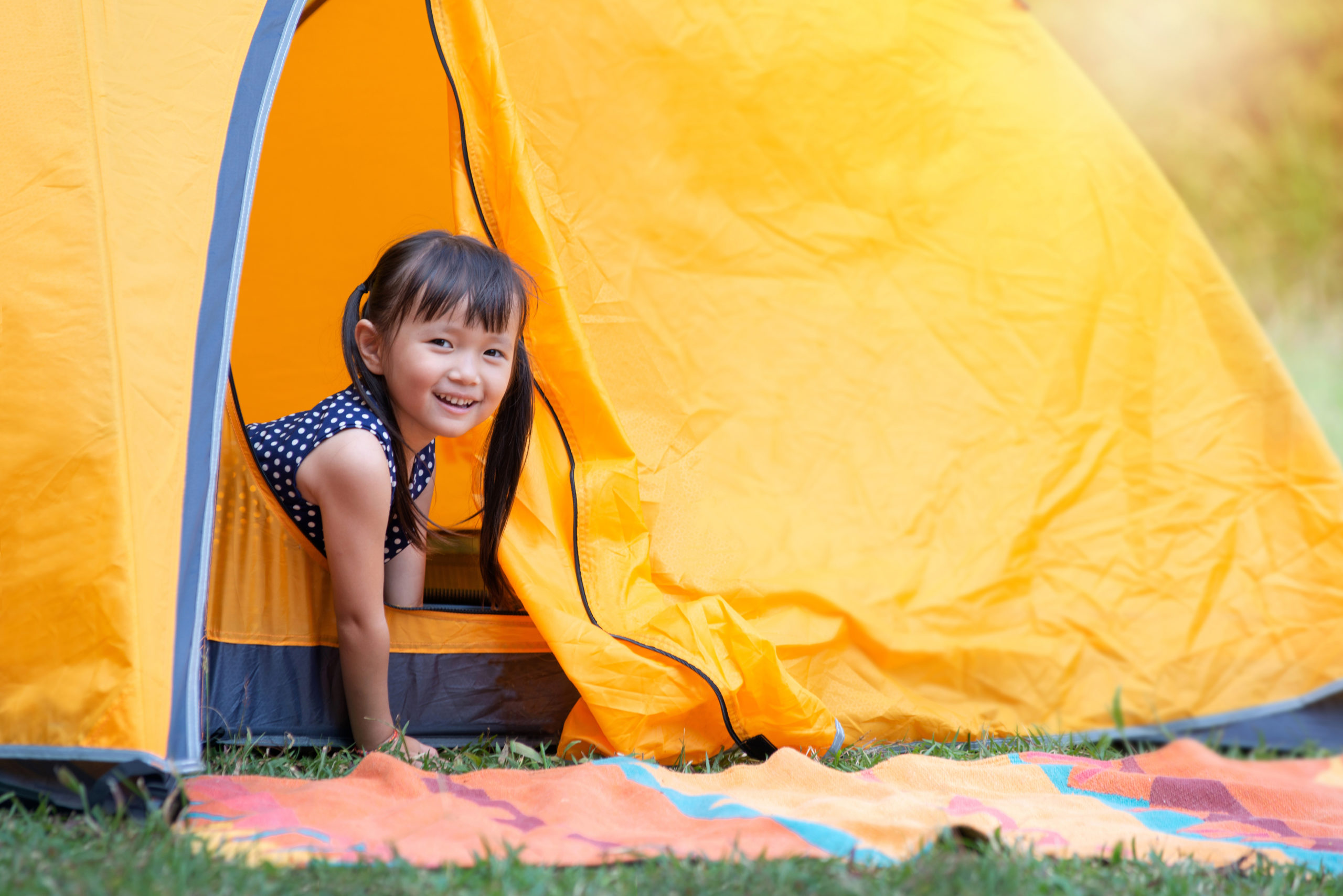 Little girl smiling and looking at camera playing with her tent on campsite, happy girl sitting inside yellow tent at park